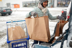 Woman loading food from shopping cart to car trunk. Consumerism, transportation and people concept - woman loading food from shopping cart to car trunk at winter Stock Image