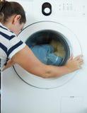 Woman loading laundry. In white washing machine Royalty Free Stock Photography