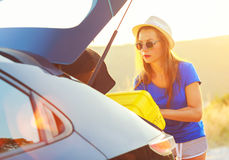 Woman loading luggage into the back of car parked alongside the. Young woman loading luggage into the back of car parked alongside the road Stock Photo