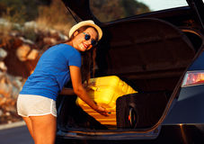 Woman loading luggage into the back of car parked alongside the Royalty Free Stock Images