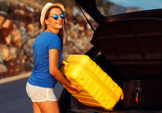 Woman loading luggage into the back of car parked alongside the Stock Photo