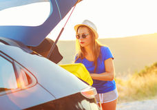 Woman loading luggage into the back of car parked alongside the. Young woman loading luggage into the back of car parked alongside the road Stock Photos
