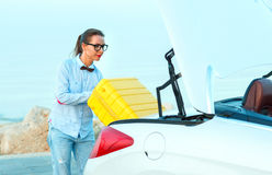 Woman loading luggage into the back of convertible car parked al. Young woman loading luggage into the back of convertible car parked alongside the road Royalty Free Stock Photos