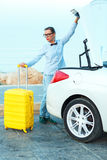 Woman loading luggage into the back of convertible car Stock Photo