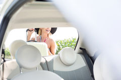 Woman loading luggage in car trunk Stock Photography