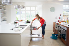 Woman Loading Plates Into Dishwasher Stock Photo