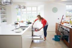 Woman Loading Plates Into Dishwasher Stock Photo