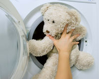 Woman loading toy in the washing machine. Woman loading fluffy toy in the washing machine Royalty Free Stock Image