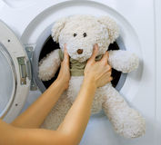 Woman loading toy in the washing machine. Woman loading fluffy toy in the washing machine Stock Photo