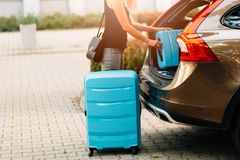 Woman loading two blue plastic suitcases to car trunk. royalty free stock photo
