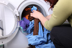 Woman loading the washing machine in bathroom Royalty Free Stock Images