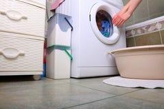 Woman loading the washing machine in bathroom. Woman loading Preparation washing machine in bathroom clothes in the washing machine Royalty Free Stock Photo