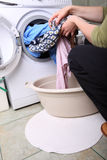 Woman loading the washing machine in bathroom Royalty Free Stock Photo