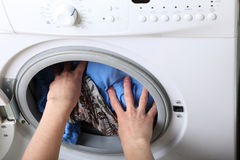 Woman loading the washing machine in bathroom Royalty Free Stock Photography