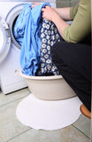 Woman loading the washing machine in bathroom Stock Image