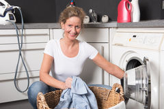 Woman loading washing machine Stock Images