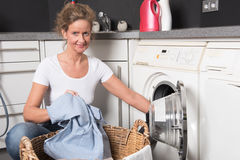 Woman loading washing machine Royalty Free Stock Photos