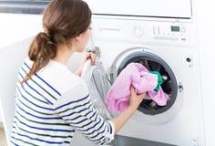 Woman loading washing machine. Woman Putting her Laundry into a Washing Machine Stock Image