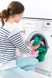 Woman loading washing machine Stock Images