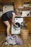 Woman loading a washing machine Stock Image