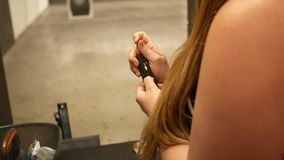 A woman loads bullets into a gun clip magazine at a firing range