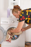 The woman loads linen into a washing machine. Stock Image