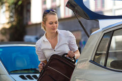 Woman loads suitcase into car boot or trunk. Woman with suitcase at opened car boot or trunk on a parking place, ready for her holidays Stock Photos
