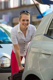 Woman loads suitcase into car boot or trunk. Woman with suitcase at opened car boot or trunk on a parking place, ready for her holidays Royalty Free Stock Photography