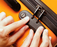 Woman locked her luggage in the orange suitcase Stock Images