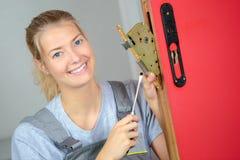 Woman locksmith fixing lock. Woman locksmith fixing a lock Stock Photography