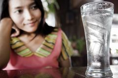 The woman lokks on a full glass of water with ice. Royalty Free Stock Images