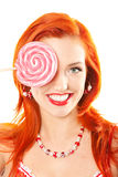 Woman with lollipop. Portrait of redhead woman covering eye with a lollipop Stock Photo