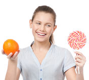 Woman with lollipop and orange. Choice Royalty Free Stock Photos
