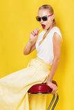Woman with lollipop in yellow skirt on red chair Royalty Free Stock Photo