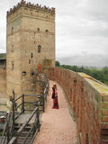 Woman in loneliness. Castle.Bygone majesty. Lonely young woman in red dress. She walks in solitude along on castle wall towards tower's door stock images