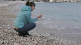 Woman at lonely cold beach. Attractive caucasian woman playing with stones near the water on the beach. stock video