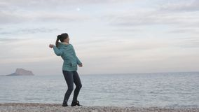 Woman at lonely cold beach. Caucasian woman throws stones into the calm sea on mountain and full moon background. stock video footage