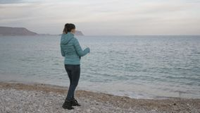Woman at lonely cold beach. Caucasian woman throws stones into the calm sea. stock video footage