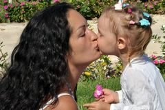 A woman with long black curly hair kisses her daughter on a sunny day. royalty free stock image