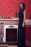 Woman in long black dress in front of chimney Royalty Free Stock Photography