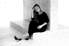 Woman in long black dress sitting against tiled wall on street Stock Photos