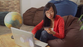 Woman with long black hair rotate the globe choose country. Young asian purchaser buy ticket online booking vacation trip on the computer sitting on the bean stock video
