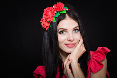 Woman with long black hair and wreath with red flowers on a dark background Royalty Free Stock Photography