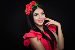Woman with long black hair and wreath with red flowers on a dark background Royalty Free Stock Photos