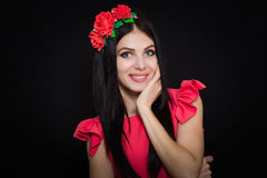 Woman with long black hair and wreath with red flowers on a dark background Stock Photography