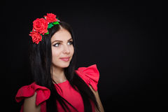 Woman with long black hair and wreath with red flowers on a dark background Stock Images