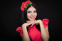 Woman with long black hair and wreath with red flowers on a dark background. Smiles. Close-up. Space for text Royalty Free Stock Photo