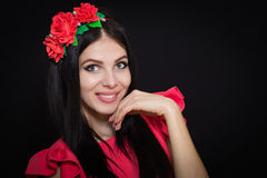 Woman with long black hair and wreath with red flowers on a dark background. Smiles. Close-up. Space for text Stock Photo