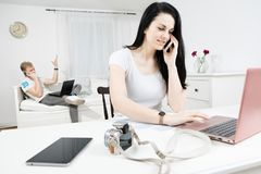 Woman with long black hairs communicate via cell phone - blond man in the background calls too royalty free stock images