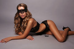 Woman with long blond curly hair in lingerie and lace mask Stock Images